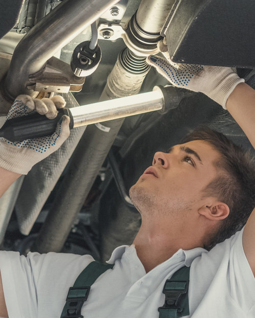 Mechanic looking under a vehicle - Car MOT Swindon